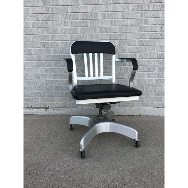Add a touch of Mad Men chic to your office with this classic rolling desk chair with brushed aluminum frame and black...