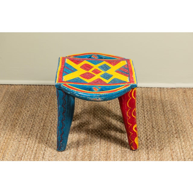 Vintage hand carved from one solid piece of wood Nupe stool from Nigeria. Bright primary colors.
