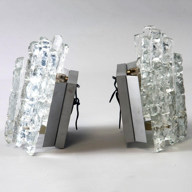 Circa 1970s pair of wall sconces attributed to Kalmar of Austria. Icicle style glass pendants arranged in two tiers around...