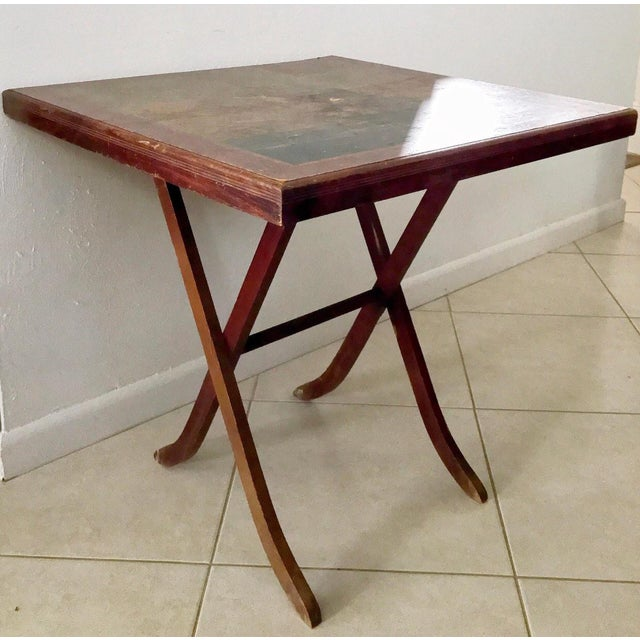 circa 1920s - early 1940s A vintage wood folding table. This small card table features a paper covered table top adorned...