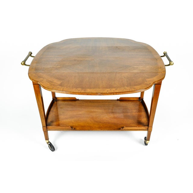 Mid-20th century satinwood mahogany wheeled bar cart or tea trolly with sides extension drop leafs. The tea trolly or bar...