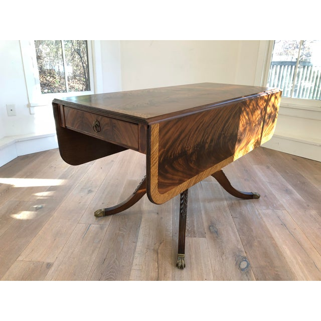 A classical style drop-leaf library table. Beautiful flame stitch mahogany top and two drawers on either end. Brass pull...