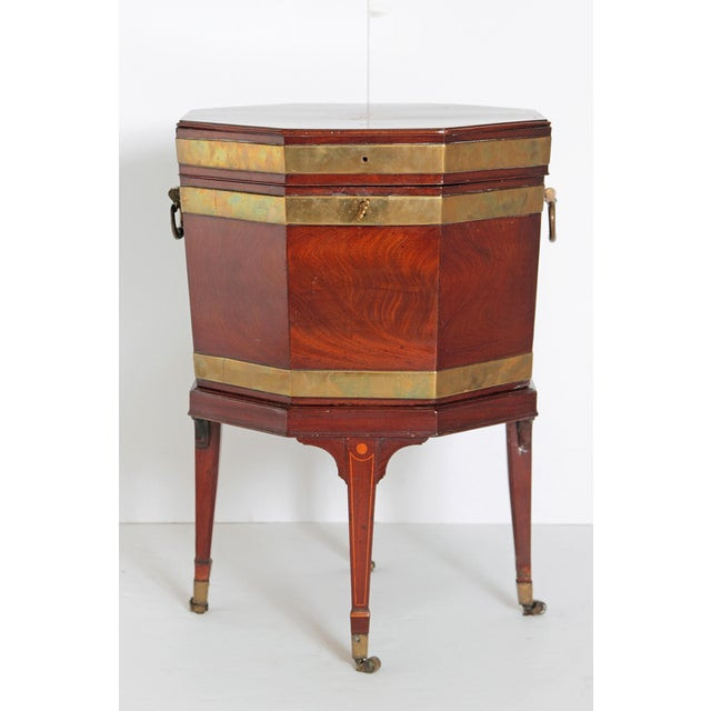 A George III brass bound mahogany octagonal cellarette on satin wood line inlaid tapering supports terminating in brass...