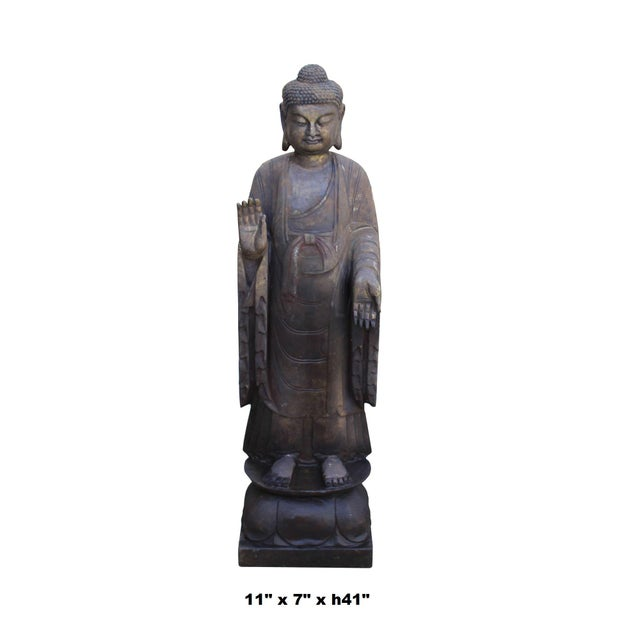 This is a standing Chinese Buddha carved from dark grayish brown color stone. It has Abhaya Mudra posture - No Fear. The...