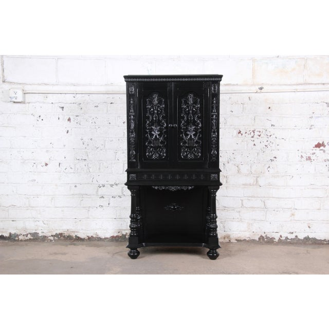 An exceptional ornate carved walnut bar cabinet, circa 1920s. The cabinet features stunning carved wood details and...
