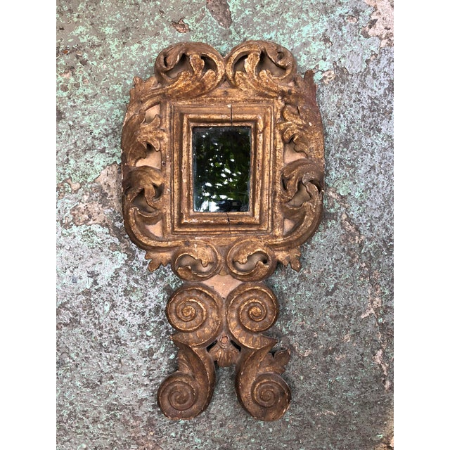 Small Italian mirror. 18th century caved giltwood. This mirror is adorned with floral and foliate patterns. Its gilding...