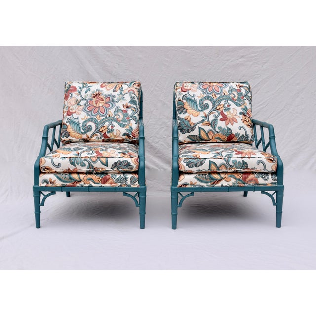 Pair of faux bamboo Chinese Chippendale lounge chairs in the style of T.H. Robsjohn-Gibbings. New floral upholstery. Newer...