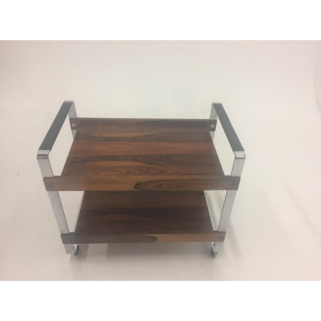 A sophisticated sleek rosewood and chrome bar cart attributed to Milo Baugham having two tiers and smooth chrome casters....