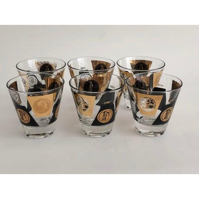 A set of 12 Mid-century black and gold leaf shot glasses with coins and insignia design. Great look on a bar cart. Half...