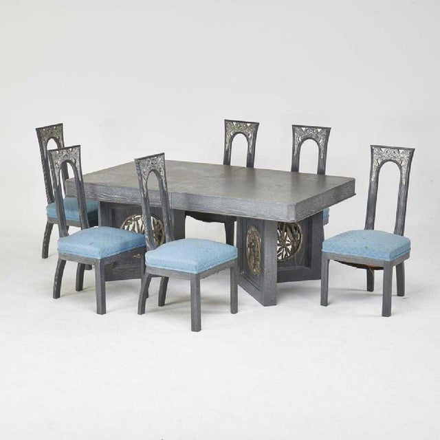A grand and sophisticated carved, cerused and silvered oak extension dining table and six side chairs by James Mont for...