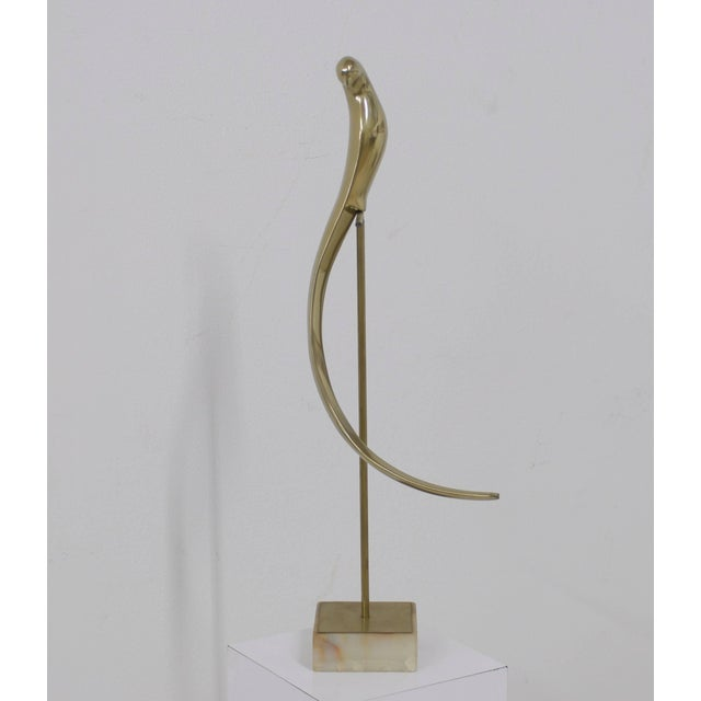 """Beautiful brass bird sculpture mounted on an onyx marble stand. We had it professionally polished. The base measures 5"""" x..."""