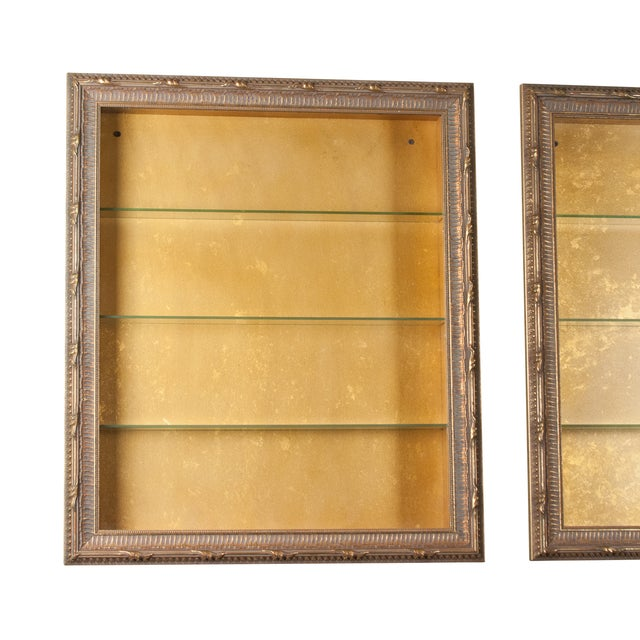 Pair of wall mounted vitrines, carved gilt wood frames, glass front hinged doors, each with four interior shelves, mottled...