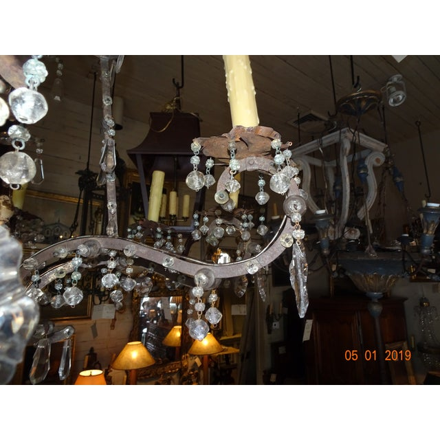 A very unique Italian chandelier in its design. Iron frame and Iron arms pierced with crystals, flower tole bobeche with...