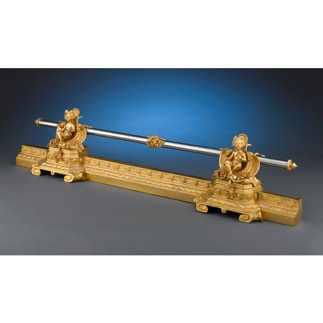 A pair of putti chenets guards this classical French ormolu fireplace fender. Expertly crafted in the Rococo Revival...