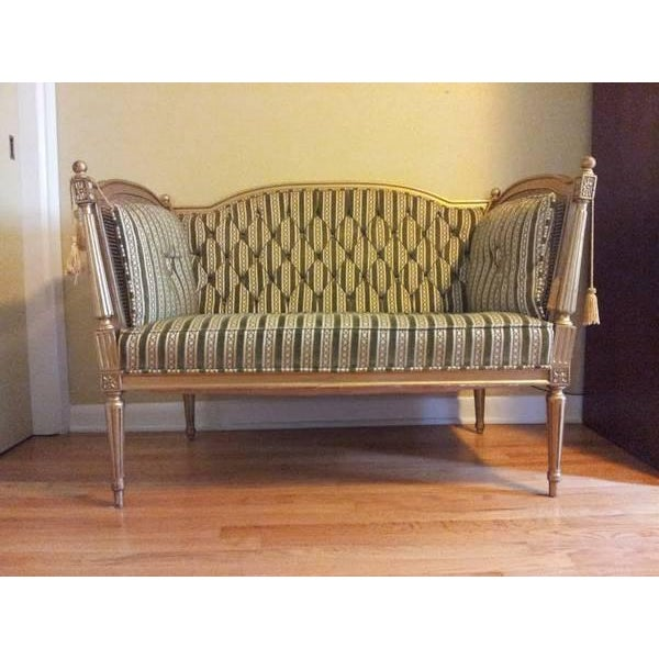 Antique 19th-Century Louis XVI-style settee couch is crafted from engraved wood and is painted in gold and features green...
