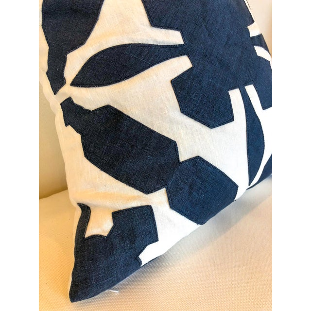 White linen pillow with navy geometric overlaid detail.