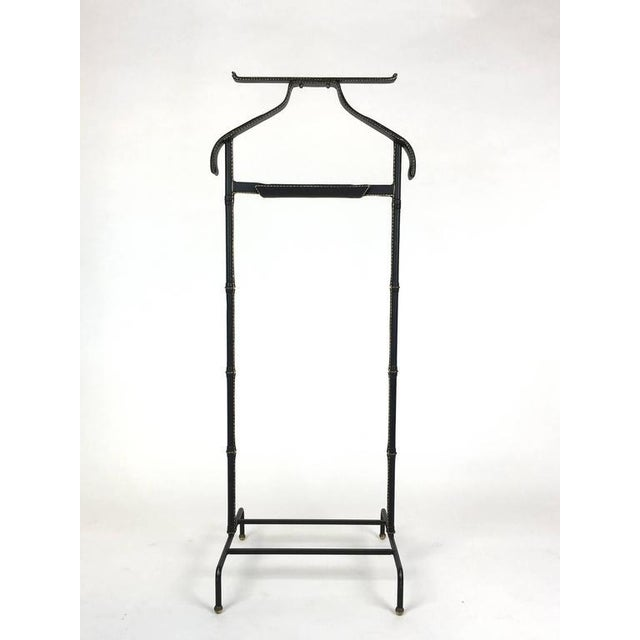 A good leather wrapped valet stand by Jacques Adnet. Iron frame wrapped in black leather with contrast stitching and brass...