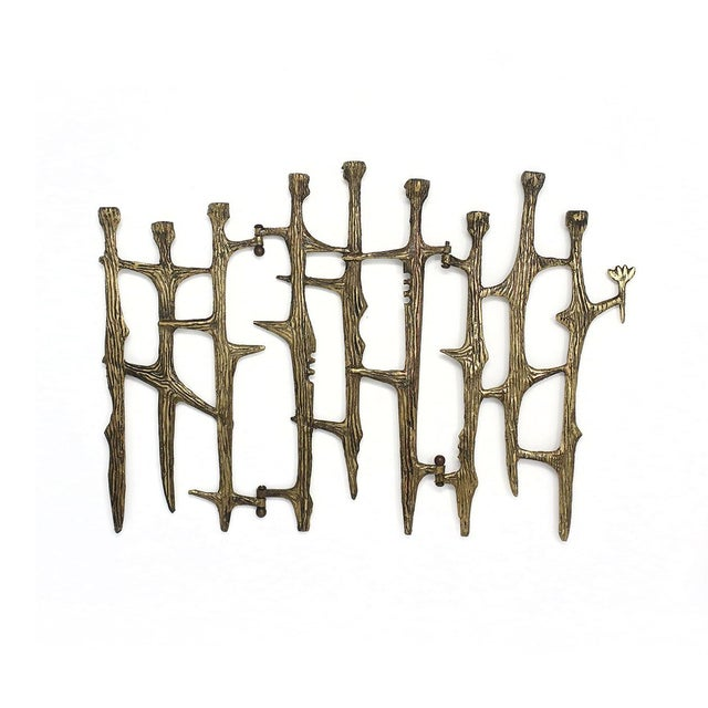 A vintage brutalist brass candleholder that could be used as a menorah or hanukkiah. With a rich patina and thornlike...