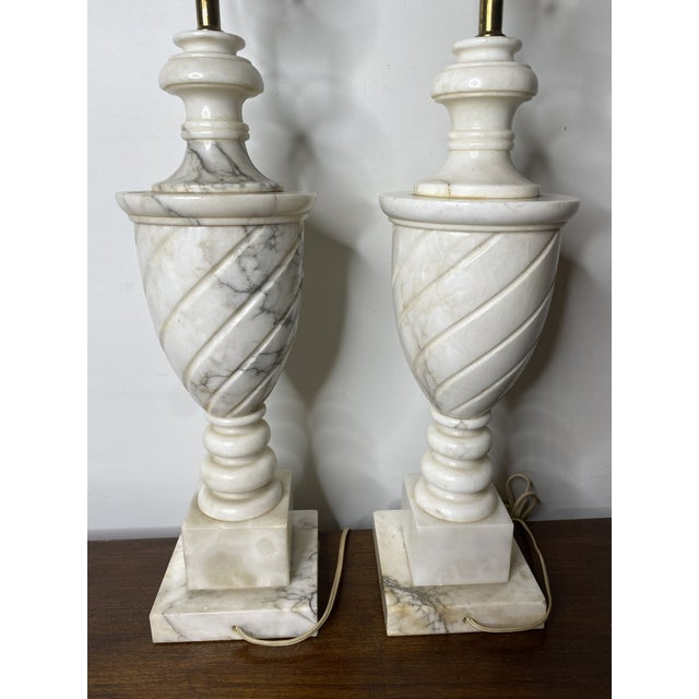 Lovely pair of large classically shaped ivory and gray marble table lamps. The length given is to the top of the socket.