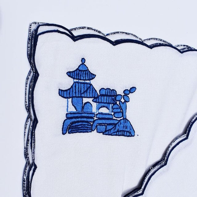 A beautiful set of four chinoiserie blue and white embroidered placemats and matching napkins. The edges of both the cloth...