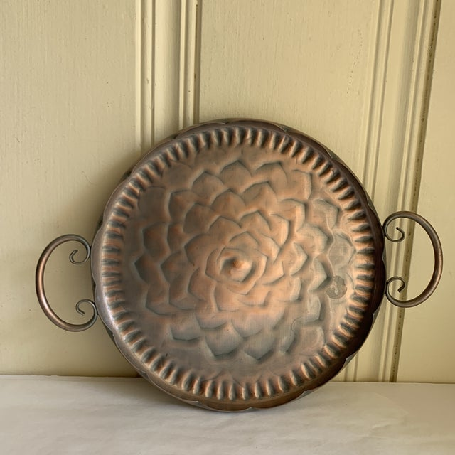 Vintage forged copper scalloped tray with floral burst center design and swirled side handles. Excellent for serving or...