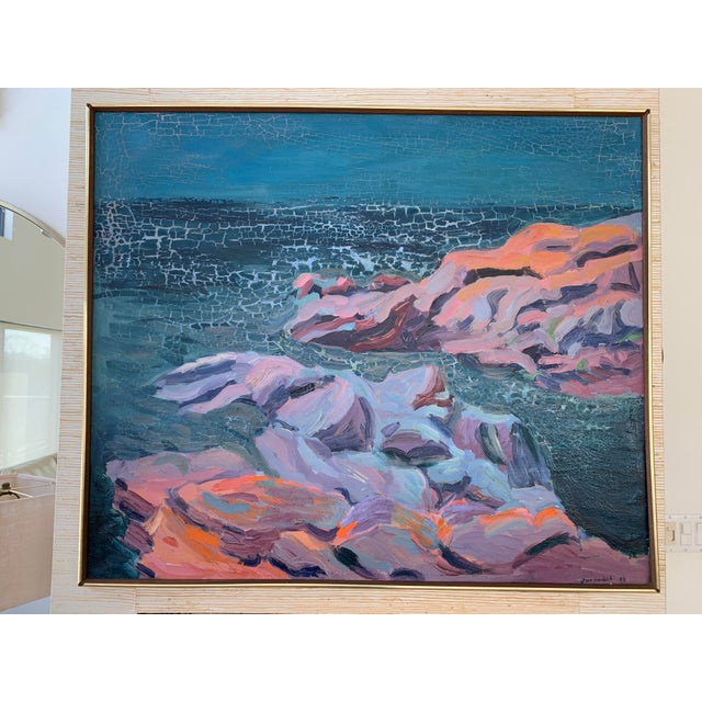 Large original seascape painting depicting a sparkling sea and a rocky, sunlit coastline in vivid cerulean blue and coral....