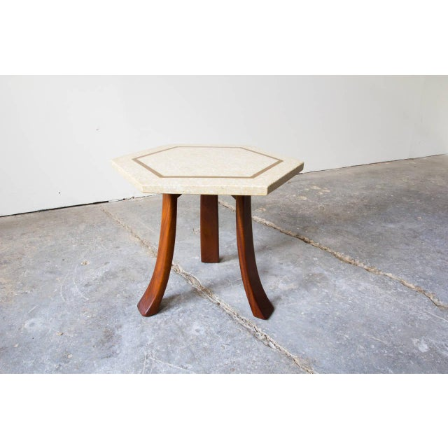 A rare three-legged hexagonal side table by Harvey Probber. The heavy terrazzo top is supported by three bent mahogany...