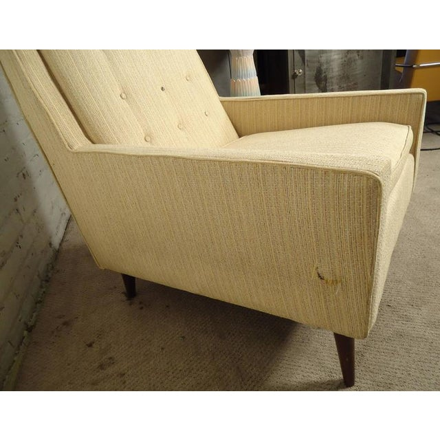 Vintage-modern lounge chair featuring tapered legs and tufted high back. Designed in the manner of Paul McCobb. Please...