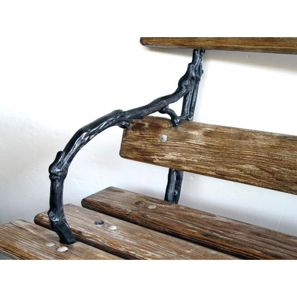 A long and well-crafted French art nouveau pine garden bench with faux bois ironwork; the slatted pine back and seat...