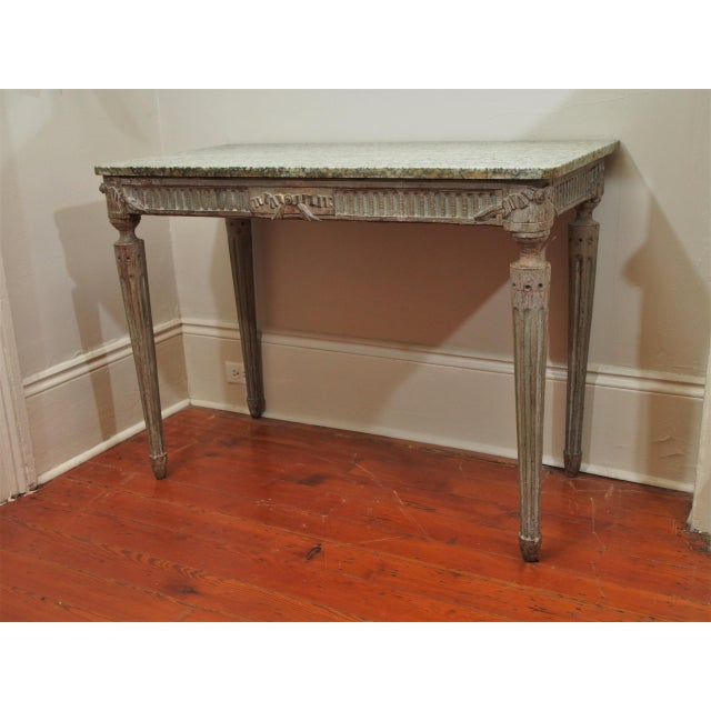 An elegant Louis XVI style console table with a beautiful and rare vert d'Estours marble top over a finely carved and...