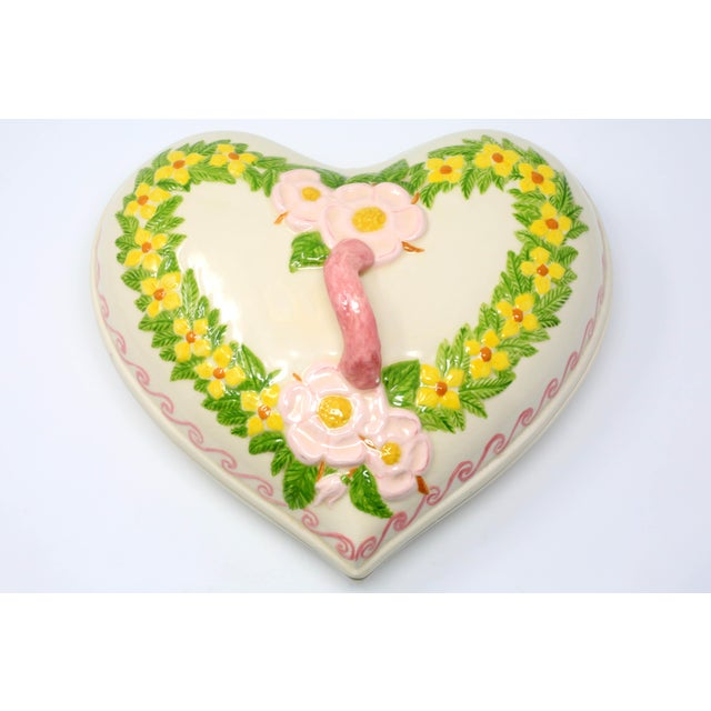 A vintage, ceramic box in the form of a heart, with hand-painted pink, yellow and green floral design. Good vintage...