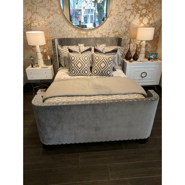 Queen-size bed frame in a slate grey velvet with large nickel nailheads and espresso stained wood legs, designed and...