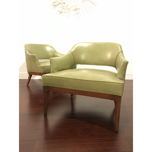 Mid century modern low slung club chairs by Harvey Probber. Chairs feature sculpted walnut legs with a curved front, and...