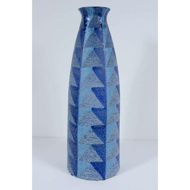 A tall ceramic vase with a mottled glaze geometric design in blues and greys to the exterior and a sleek high gloss black...