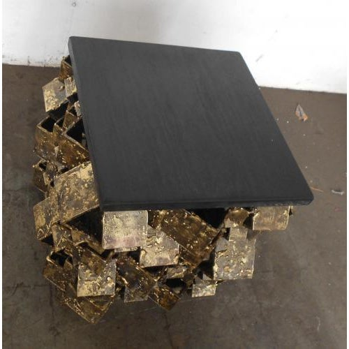 The Faceted Side Table is shown in fused bronze with a slate top. The table is available in a variety of metal finishes.