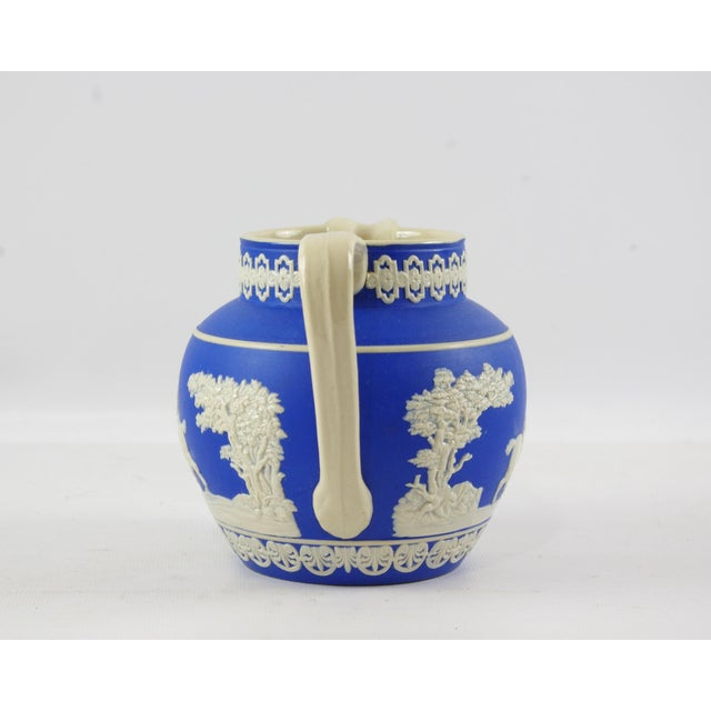 A round and squat jasperware pitcher with applied hunting scene. There are men on horseback, hounds taking down a stag,...