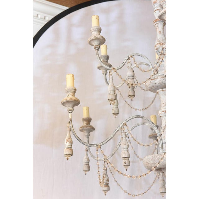 Unusual chandelier, having a distressed painted finish; its turned knopped centre column, with two tiers of six S-scroll...