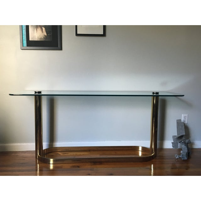 """Brass base with thick 1/2"""" glass top secured by brass caps that screw into place. Brass shows wear consistent with age. A..."""
