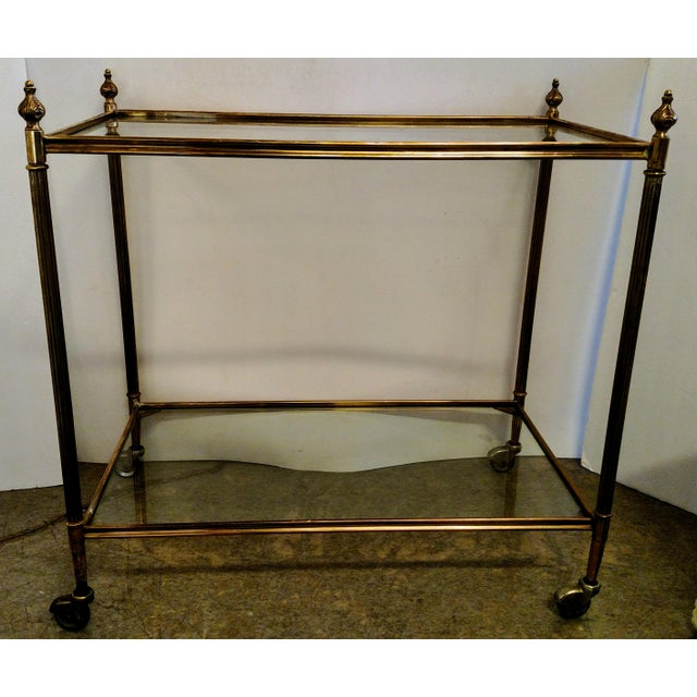 Great vintage two tier brass and glass bar cart with nicely detailed cast brass finials and fluted posts. The caster...
