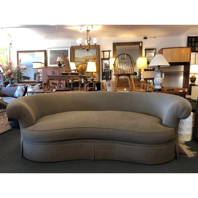 Design Plus Gallery presents an elegant custom sofa. Softly curved back and seat, the muted color sofa features rolled...