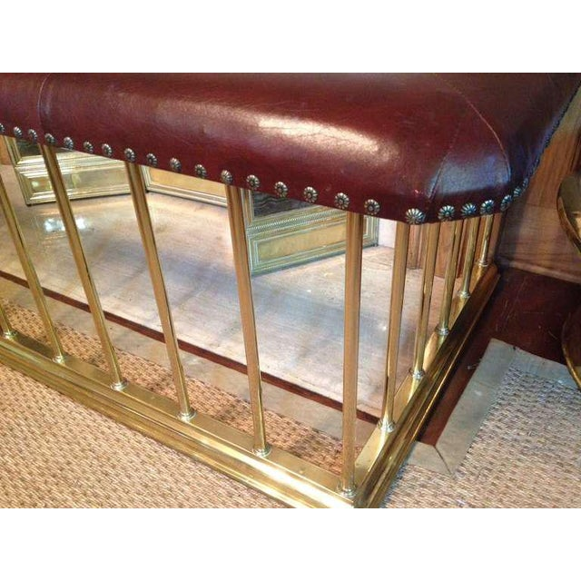 Large English Edwardian brass club fender upholstered with original dark chestnut colored leather, with brass railheads....