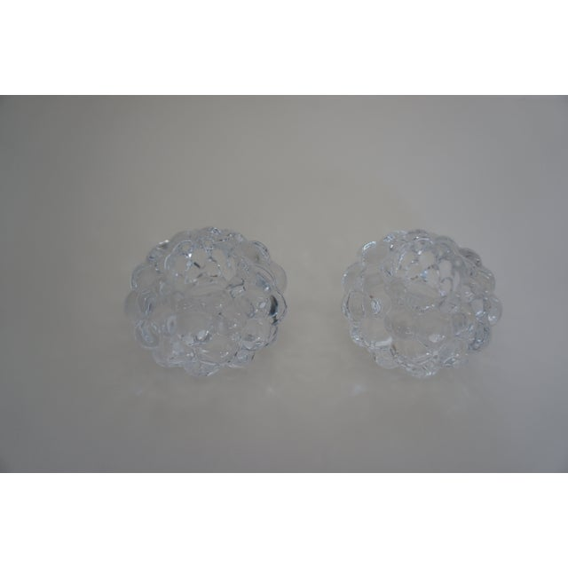 A pair of heavy crystal votive candle holders designed by Anne Nilsson for Orrefors Sweden. Shape reminiscent of raspberry...