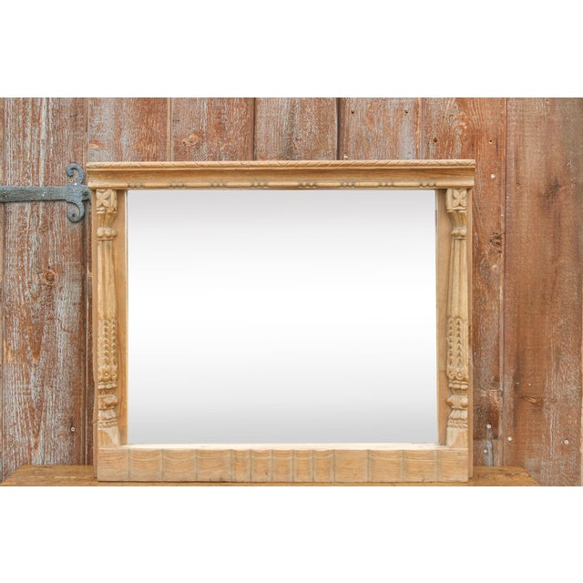 A stunning wall mirror made from an antique window frame from India featuring column borders adorned with floriate...
