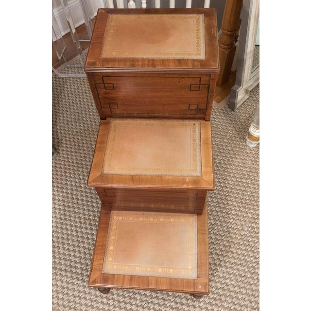 A handsome set of library steps in light mahogany with a lovely tan tooled leather, ebonized inlaid design on front of...
