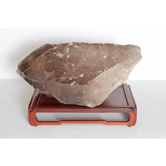 A large piece of smoky quartz on a large carved Chinese stand.