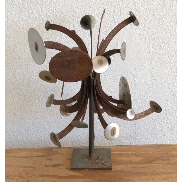 A brutalist style hand torched sculpture by Frank Cota. The metal sculpture is mounted on a stand and has arms emanating...