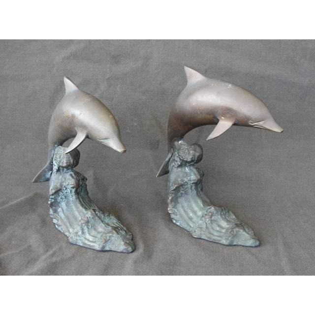"A vintage pair of 7 1/2"" bronze bookends of dolphins cresting a wave. Each book end measures 7 1/2"" tall and 6 1/2"" long...."