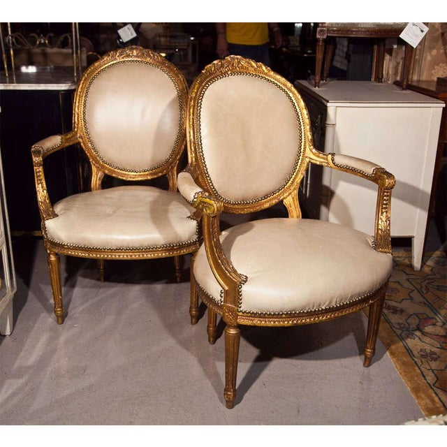 A pair of lovely French fauteuils in the taste of Louis XIV, circa 1940s. The frames are beautifully gilded. They feature...