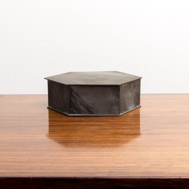 This octagon shaped box has a crown stamped on the bottom, and red fabric on the inside. From the 1950s, this box would be...