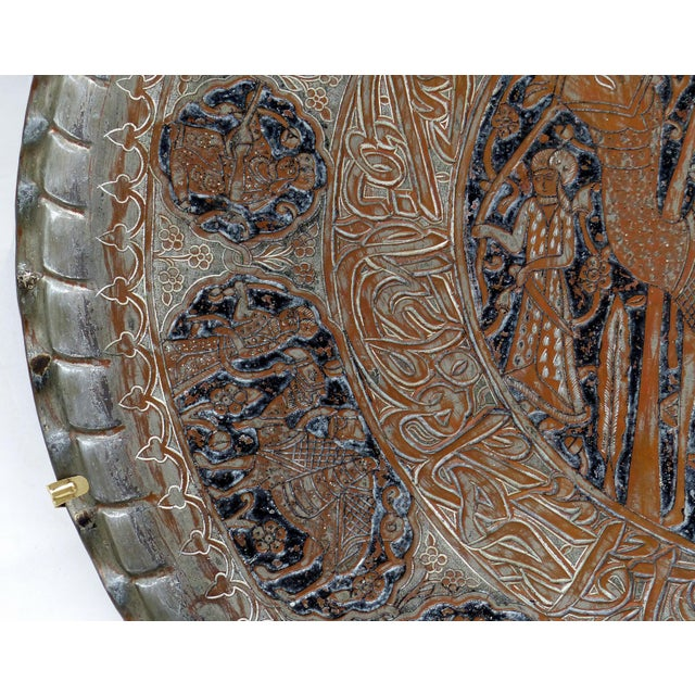 Offered for sale is a copper tray from Syria with a scalloped edge and a central etched camel cartouche surrounded by...